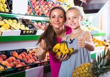 Mujer emocionada con la hija en mercado de la fruta Imágenes de archivo libres de regalías