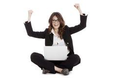 Mujer emocionada con los brazos para arriba que gana en línea Foto de archivo libre de regalías