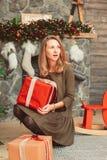 Mujer emocionada con los presentes en interior de la Navidad imagenes de archivo