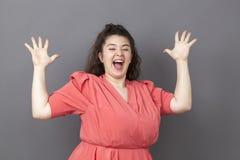 Mujer emocionada del tamaño extra grande que se goza con lenguaje corporal dinámico Imagen de archivo libre de regalías