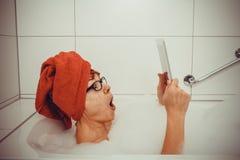 Mujer emocionada en bañera con las tabletas fotos de archivo
