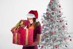 Mujer emocionada en el sombrero de santa que mira el regalo de la Navidad Imágenes de archivo libres de regalías