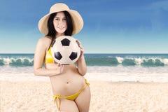 Mujer emocionada en el traje de baño que sostiene el balón de fútbol Foto de archivo
