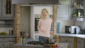 Mujer emocionada en la cocina que hace una danza tonta y que prepara la comida almacen de video