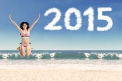 Mujer emocionada en la playa con los números 2015 Imagenes de archivo