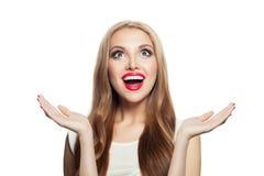 Mujer emocionada feliz aislada en el fondo blanco Muchacha sorprendida con maquillaje rojo de los labios y el pelo sano que miran imagen de archivo libre de regalías