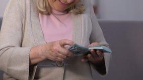 Mujer emocionada feliz que cuenta los billetes de banco del dólar, actividades bancarias y acreditándolos, seguro almacen de metraje de vídeo