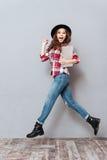 Mujer emocionada joven en el sombrero que celebra el ordenador portátil y el salto fotografía de archivo libre de regalías
