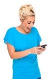 Mujer emocionada por el mensaje de texto en el teléfono celular Foto de archivo