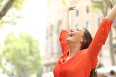 Mujer emocionada que aumenta los brazos en la calle Foto de archivo libre de regalías
