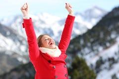 Mujer emocionada que aumenta los brazos en una montaña nevosa Fotos de archivo