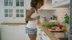 Mujer emocionada que canta mientras que cocina almacen de video