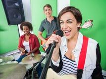 Mujer emocionada que canta mientras que banda que toca el instrumento musical imagen de archivo