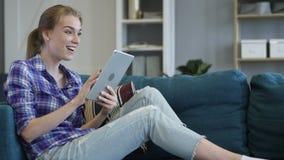 Mujer emocionada que celebra éxito mientras que usa la tableta almacen de video