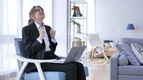 Mujer emocionada que celebra el éxito, trabajando en el ordenador portátil metrajes