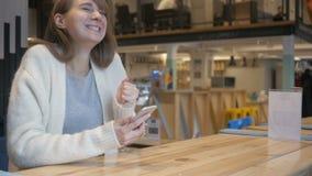 Mujer emocionada que celebra las noticias en Smartphone, triunfo del juego