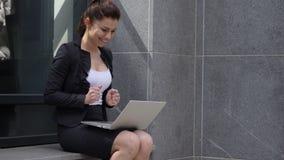 Mujer emocionada que celebra resultados en el ordenador portátil que se sienta fuera de oficina almacen de metraje de vídeo