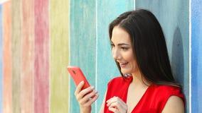 Mujer emocionada que comprueba el teléfono en una pared colorida almacen de metraje de vídeo