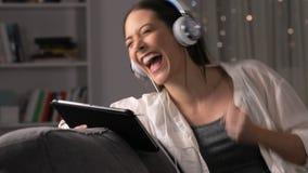 Mujer emocionada que encuentra el contenido en línea en la tableta almacen de metraje de vídeo