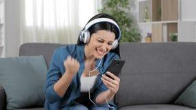 Mujer emocionada que escucha la música en línea almacen de metraje de vídeo