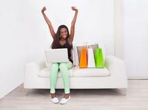 Mujer emocionada que hace compras en línea en casa Foto de archivo libre de regalías