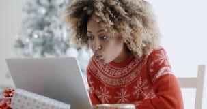 Mujer emocionada que hace compras en línea para los negocios de Navidad Foto de archivo