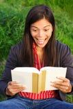 Mujer emocionada que lee un libro Foto de archivo libre de regalías