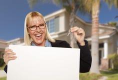 Mujer emocionada que lleva a cabo llaves de la casa y la muestra en blanco de Real Estate Fotos de archivo libres de regalías