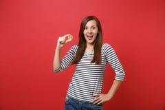 Mujer emocionada que mantiene la boca abierta de par en par, pareciendo sorprendido, sosteniendo la moneda del metal del bitcoin  fotografía de archivo libre de regalías