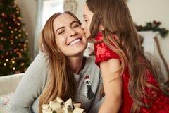 Mujer emocionada que recibe el regalo de la Navidad de hombre en casa imagen de archivo