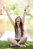 Mujer emocionada que se sienta con los brazos levantados Foto de archivo libre de regalías