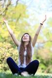Mujer emocionada que se sienta con los brazos levantados Fotos de archivo libres de regalías