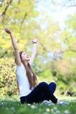 Mujer emocionada que se sienta con los brazos levantados Imagenes de archivo