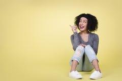 Mujer emocionada que señala en el copia-espacio Imagen de archivo libre de regalías