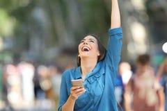 Mujer emocionada que sostiene el teléfono y que aumenta el brazo foto de archivo libre de regalías