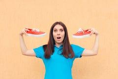 Mujer emocionada que sostiene un par de zapatos rojos del deporte fotos de archivo libres de regalías