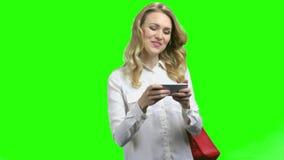 Mujer emocionada que usa smartphone en fondo de pantalla verde almacen de metraje de vídeo