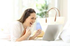 Mujer emocionada que usa un ordenador portátil en vacaciones Fotos de archivo