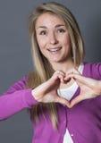 Mujer emocionada 20s que muestra forma del corazón con las manos Foto de archivo