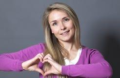 Mujer emocionada 20s que muestra forma del corazón con las manos Fotos de archivo libres de regalías