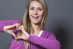 Mujer emocionada 20s que muestra forma del corazón con las manos Imágenes de archivo libres de regalías