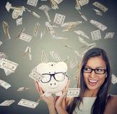Mujer emocionada sobre ahorros debajo de la lluvia del dinero que cae abajo dólares Imagen de archivo