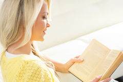 Mujer emocionada sonriente hermosa que lee un libro por la mañana Fotografía de archivo