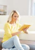 Mujer emocionada sonriente hermosa que lee un libro por la mañana Imagen de archivo
