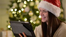 Mujer emocional en Santa Hat Using Gadget During la celebración de Navidad Morenita asombrosa con el pelo largo y encantar metrajes