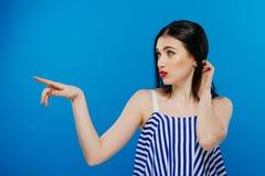 Mujer emocional hermosa de risa del estilo de pelo rizado que mira para arriba con la mano cerca de la cara en fondo azul brillan Imagen de archivo