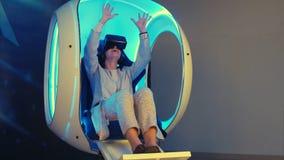Mujer emocional que experimenta realidad virtual en una silla interactiva móvil Imagen de archivo