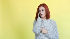 Mujer emocionalmente pelirroja que lleva el suéter gris acogedor que habla en el teléfono de la llamada almacen de video