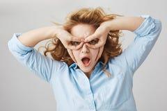Mujer emotiva joven que es infantil, haciendo la máscara con las manos y mirando a través de los fingeres, haciendo caras mientra Fotos de archivo libres de regalías