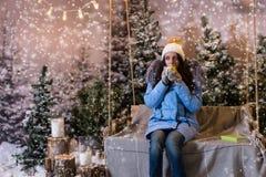 Mujer en abajo chaqueta azul que bebe la bebida caliente mientras que se sienta en a Fotos de archivo libres de regalías